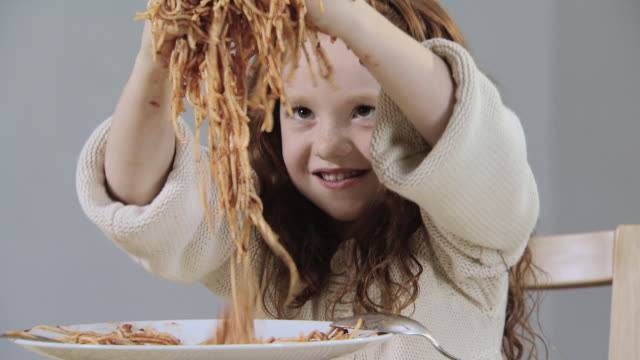 girl playing with spaghetti - unfug stock-videos und b-roll-filmmaterial