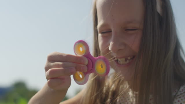 Girl Playing with Spinner Outdoors at Summer