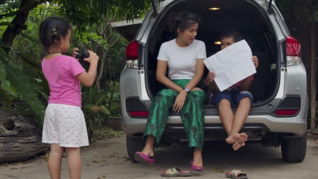 a girl playing with telescope looking at family talking sitting in the car trunk explaining the zoo's map - aunt, a boy, a girl. - road map stock videos & royalty-free footage
