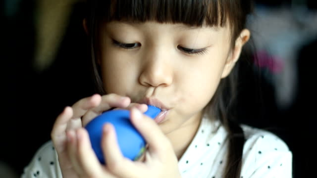 Girl playing with the blue balloon