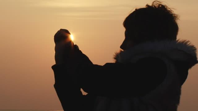 Mädchen spielt mit den Sonnenuntergang