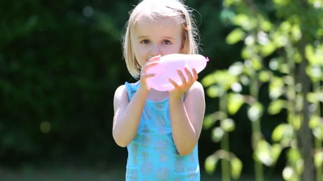 vídeos de stock e filmes b-roll de girl (4-5) playing with water balloon - bomba de água equipamento