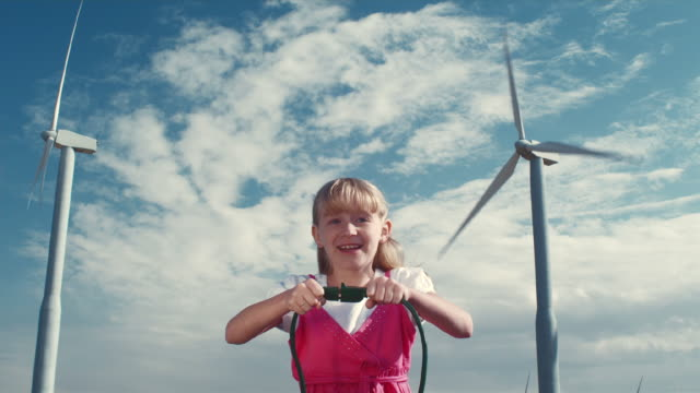 ms girl plugging cords together in front of wind turbines / zillah, washington, usa   - alternative energy stock videos and b-roll footage