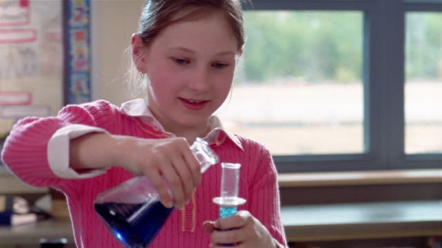 Girl pouring clear blue solution into test tube in science class / holding test tube up / pouring solution back into beaker / Gorham, Maine
