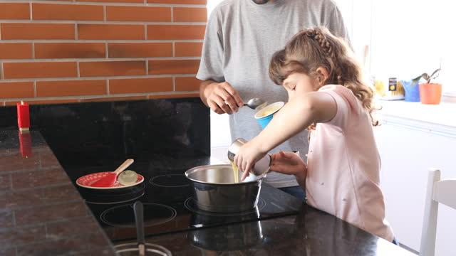 彼女の父親が見守る鍋にコンデンスミルクを注ぐ女の子 - dia点の映像素材/bロール