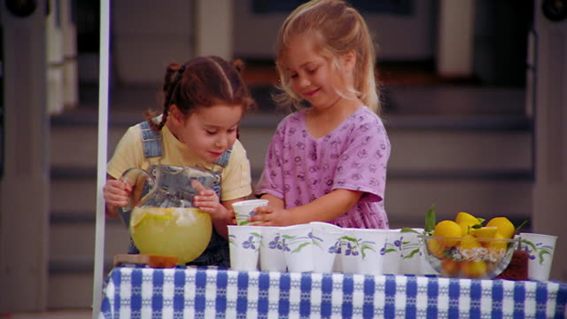 ms girl pouring lemonade in to cup held by blond girl at lemonade stand / girls laughing - lemonade stock videos and b-roll footage