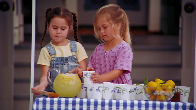 MS girl pouring lemonade into cup held by blond girl at lemonade stand in front of house