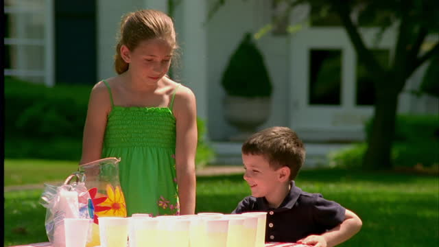 a girl pours a glass of lemonade for a small boy at a lemonade stand. - lemonade stock videos and b-roll footage