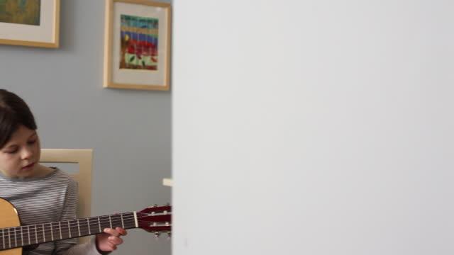 MS PAN Girl (10-11) practicing guitar in her bedroom / Perth, Western Australia, Australia