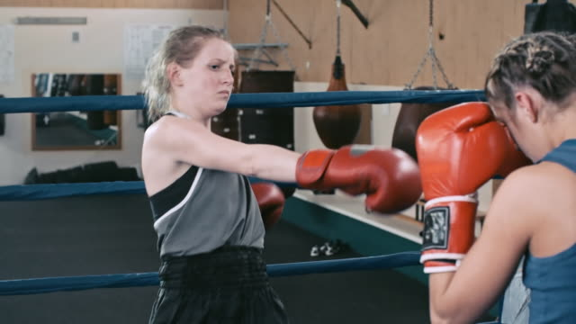Girl practicing kicks with partner in boxing ring