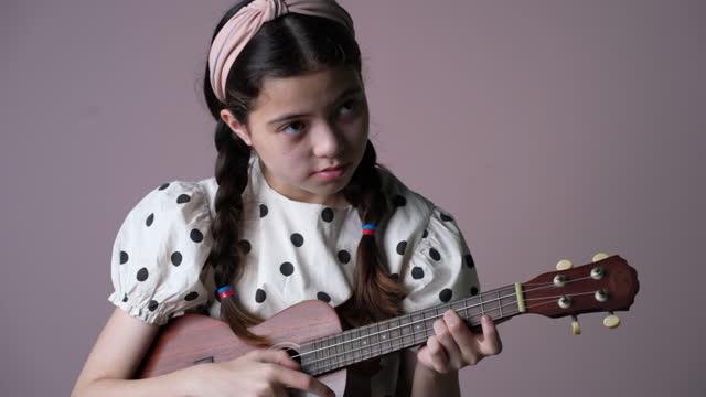 vídeos de stock, filmes e b-roll de garota praticando ukulele. - ukulele