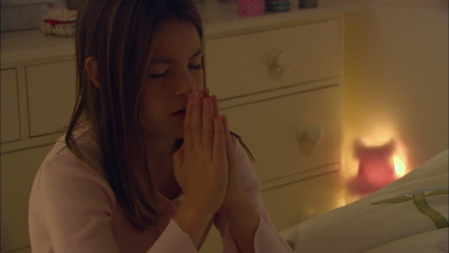 cu, girl (10-11) praying in bedroom at night - 10 11 jahre stock-videos und b-roll-filmmaterial
