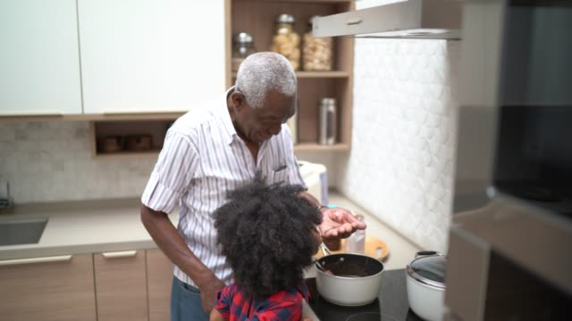 girl preparing/cooking brigadeiro with her grandfather - homemaker stock videos & royalty-free footage