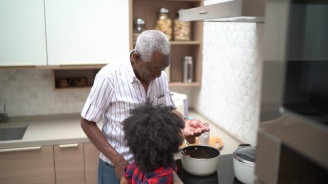 ragazza che prepara/cucina brigadeiro con il nonno - persona di casa video stock e b–roll