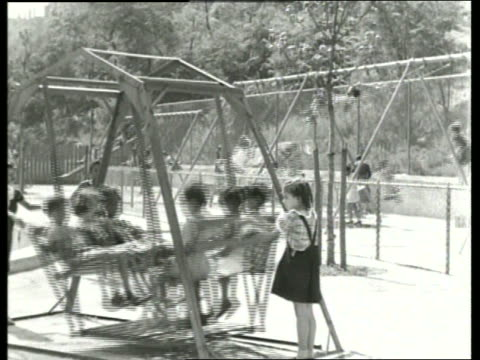 b/w girl pushing children on bench swing on playground / sound - pushing stock videos and b-roll footage