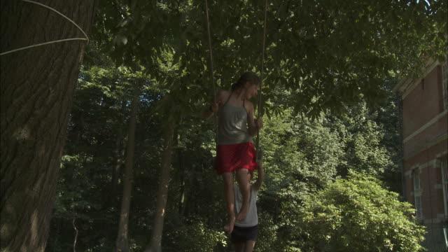 ms girl (12-13) pushing friend (10-11) on rope swing in garden, bouillon, belgium - rope swing stock videos & royalty-free footage