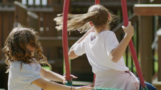 girl pushing funny friend in tire swing at playground / pleasant grove, utah, united states - tire swing stock videos & royalty-free footage