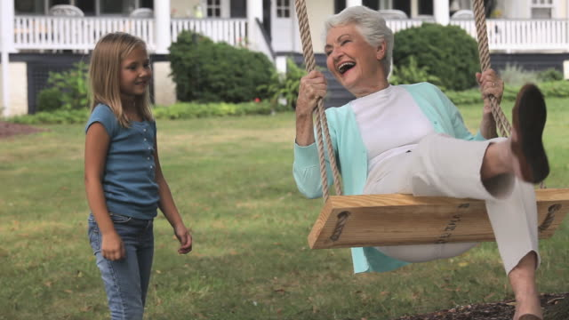 ms girl (6-7) pushing grandmother on swing in backyard of home / richmond, virginia, usa - enkelin stock-videos und b-roll-filmmaterial