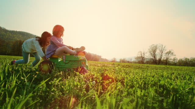 slo mo ts girl pushing her younger sister on a toy tractor across the sunny meadow - top capo di vestiario video stock e b–roll
