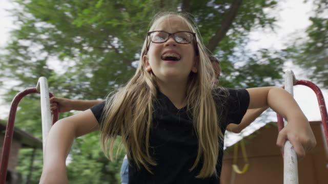 girl pushing smiling friend on neighborhood playground merry-go-round / provo, utah, united states - polynesian ethnicity stock videos & royalty-free footage