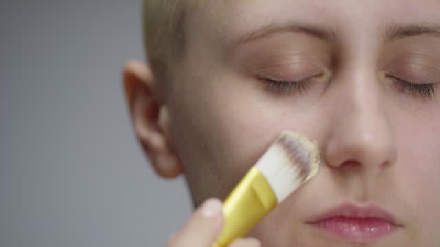 女の子は彼女の顔に基礎を置きます。ファッションビデオ。メイクアップ。4k 30fps プロレス 4444 - アイシャドウ点の映像素材/bロール