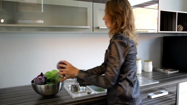 Girl puts fresh vegetables into bowl