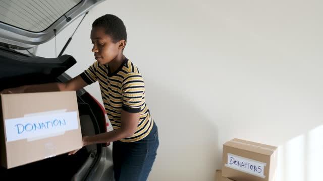 vídeos y material grabado en eventos de stock de chica poniendo cajas con donaciones en el coche. - sólo mujeres jóvenes