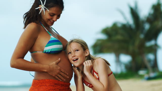 vídeos de stock e filmes b-roll de girl putting ear to pregnant woman's stomach - 12 13 anos
