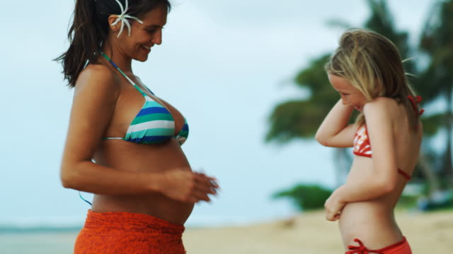 vídeos de stock, filmes e b-roll de girl putting ear to pregnant woman's stomach - biquíni