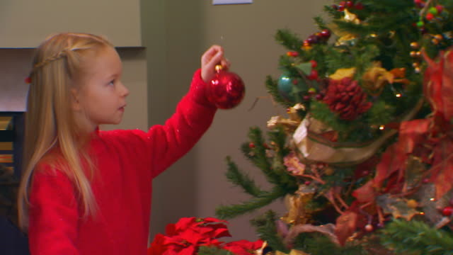 girl putting ornaments on tree, slow motion - ängel bildbanksvideor och videomaterial från bakom kulisserna