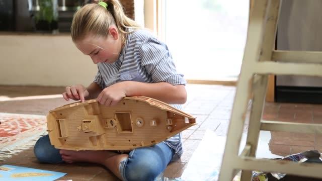 girl putting plastic ship together