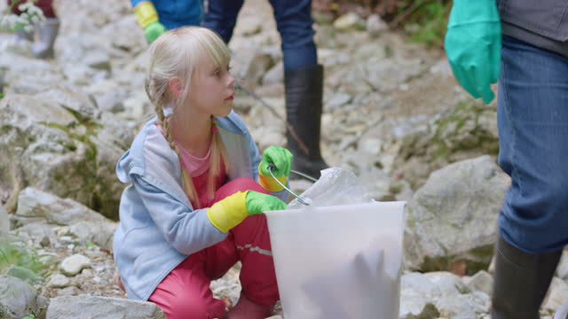 girl putting trash into a bucket and helping in the local cleanup of a forest in her community - protective glove stock videos & royalty-free footage