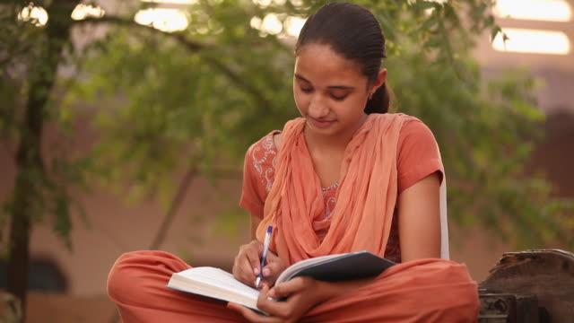 girl reading a book, faridabad, haryana, india - girl sitting cross legged stock videos & royalty-free footage