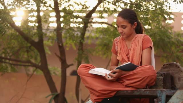 vídeos de stock, filmes e b-roll de girl reading a book, faridabad, haryana, india - roupa tradicional