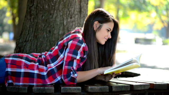 girl reading a book in the park - legs crossed at ankle stock videos & royalty-free footage