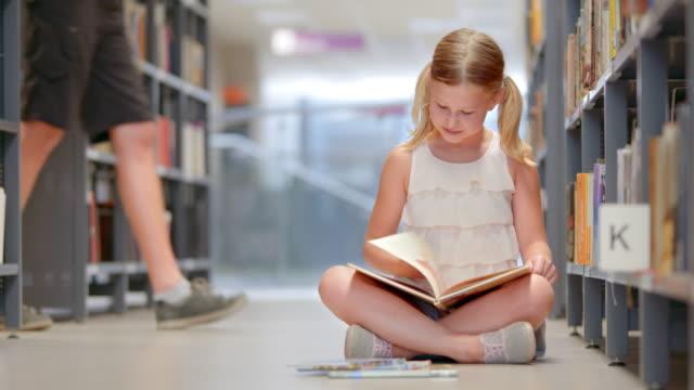 vídeos y material grabado en eventos de stock de ds niña leyendo un libro con estantería de libros en la sala de estar de la biblioteca - sin mangas