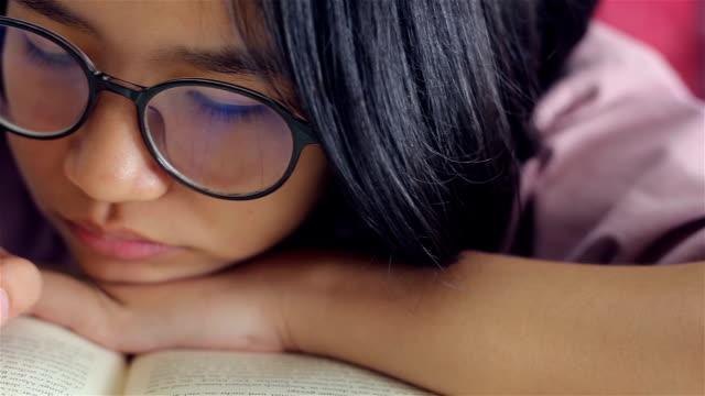vídeos de stock, filmes e b-roll de menina lendo um livro  - óculos de leitura