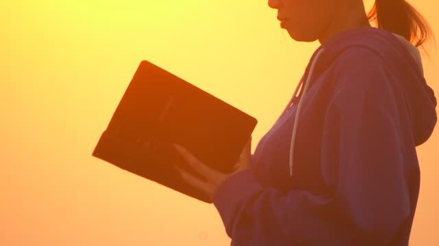 夕暮れ時に外で聖書を読む女の子 - ペンテコステ点の映像素材/bロール