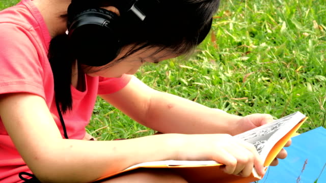 mädchen-lesebuch und musik hören. - kindertag stock-videos und b-roll-filmmaterial