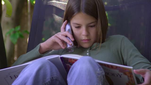 cu, girl (10-11) reading book and talking on phone in garden, hollywood, california, usa - 10 11 år bildbanksvideor och videomaterial från bakom kulisserna
