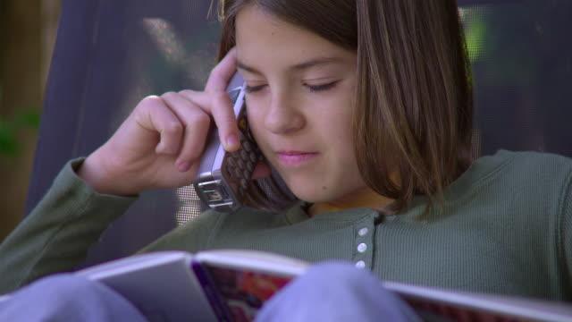 vídeos de stock e filmes b-roll de cu, girl (10-11) reading book and talking on phone in garden, hollywood, california, usa - telefone sem fio