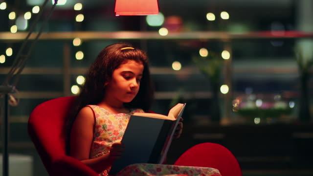 Girl reading book at night