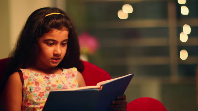 stockvideo's en b-roll-footage met girl reading book at night - reading