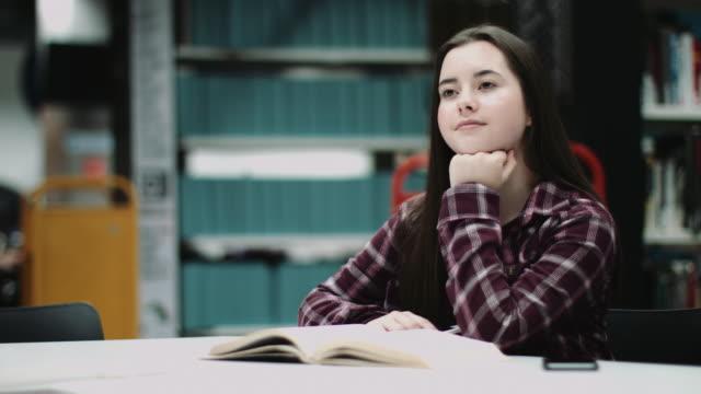 girl reading book in a library, with smart phone - endast en tonårsflicka bildbanksvideor och videomaterial från bakom kulisserna
