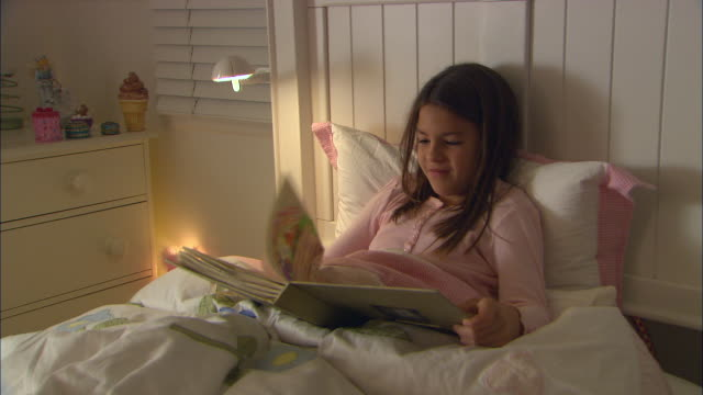 vídeos y material grabado en eventos de stock de cu, girl  (10-11) reading book in bed - recostarse