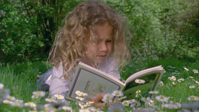 cu, girl (4-5) reading book in garden, brussels, belgium - fiaba video stock e b–roll