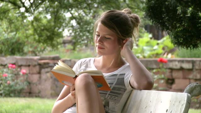 MS Girl reading book in garden / Saarburg, Rhineland-Palatinate,  Germany