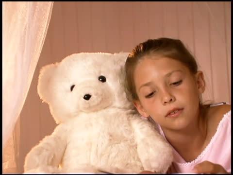 Girl reading book with teddy bear