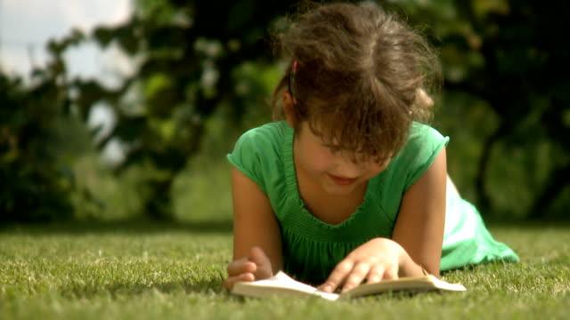 vídeos de stock, filmes e b-roll de menina lendo na park - livro