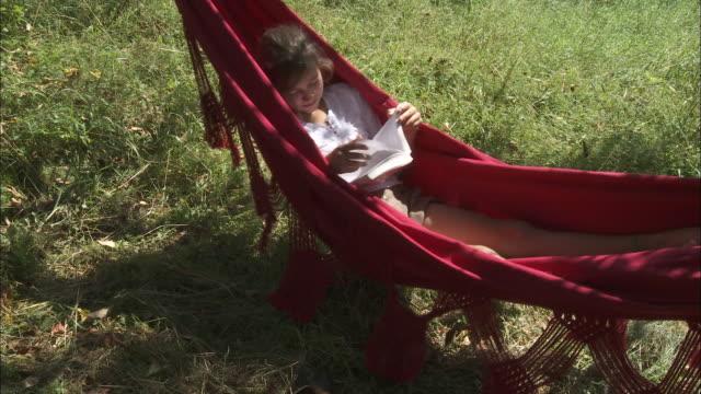 ms ha girl (10-11) reading in red hammock, bouillon, belgium - 10 11 jahre stock-videos und b-roll-filmmaterial